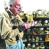 John Blanchfield stands in his Bloomingdale residence and examines one of the antique clocks he has collected over the years. Due to ill health, the 80-year-old clock repairman will close his downtown shop in Saranac Lake.  <br><br>(P-R Photo/Jack LaDuke)