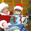 John Sanpietro, 3, of Jay helps Mrs. Claus read Christmas-themed children's books at the AuSable Forks Free Library Saturday afternoon. Area children gathered at the library for the storytime holiday event that included refreshments and craft activities. For more photos on holiday happenings in the North Country, see page A3.<br><br>(P-R Photo/Andrew Wyatt)