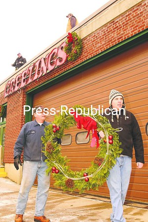 Saranac Lake volunteer firefighters Bobby Nadon and Todd Goff carry a large Christmas wreath for placement on the Fire Station. Up on the rooftop are Dave Martelle and Jeff White, attaching an illuminated greetings display.<br><br>(P-R Photo/Jack LaDuke)