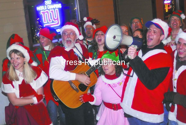 About 30 Santas and elves belt out Christmas songs Friday night in downtown Plattsburgh outside the Green Room bar as part of the annual Santa Night fundraiser event. Area residents dressed up and stopped in local bars and restaurants to entertain patrons with renditions of holiday songs and collected donations to help needy families. This year the local event raised money for the Christmas Bureau, a local, all-volunteer organization whose sole mission is to provide Christmas for low-income families throughout all of Clinton County, with the help of the local community for funds and gifts. Santa Night is held annually in locations nationwide on the second Friday in December. <br><br>(P-R Photo/Andrew Wyatt)