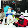 "The Methot family of Tupper Lake gathers around the snowman they built for a competition Saturday in Berkley Green Park in downtown Saranac Lake. The family tied for first place with their creation ""Candyman."" Participants in the snowman building contest said that with the temperature at just above freezing, it made conditions perfect for making a snowman.<br><br>(P-R Photo/Jack LaDuke)"