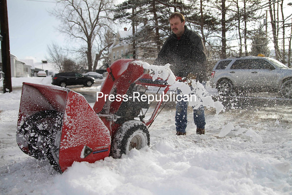 Travis Deyo of Beekmantown works Friday afternoon on clearing the driveway of an apartment building in Plattsburgh, one of seven he owns and operates. Using the plow on his pickup truck and his snowblower, it takes him about three hours total to clear all of his properties. The Plattsburgh area received about two inches of snow, the second measurable snowfall this week.<br><br>(P-R Photo/Gabe Dickens)
