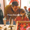 Five-year-old Charlotte Hughes and her dad, Ken Hughes, admire the holiday ornaments on display at the Essex Ice Cream Shop. The all-natural ornaments were created by the Lakeside Preschool in Essex and are being used as a fundraiser for the school.<br><br>(P-R Photo/Joanne Kennedy)