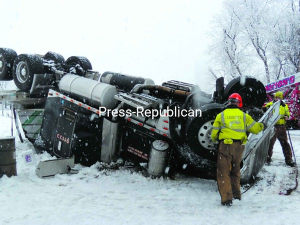 A tow-truck team from Lauzon Auto Tech in Malone makes preparations to right an overturned tractor trailer that flipped Wednesday morning during the heavy snowstorm. Malone-based State Police said the driver, Christopher Kelly of TLC in Des Moines, Iowa, will likely be ticketed for failure to reduce speed for hazardous conditions.<br><br>(Staff Photo/Denise A. Raymo)