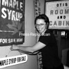 """Curator Jenifer Kuba of the Adirondack History Center Museum in Elizabethtown straightens a sign in the exhibit """"A Sign of the Times."""" Kuba became intrigued with doing the project after seeing a sign denoting, """"Eugene Cram — Horseshoeing and Job Work."""" The many signs in the exhibit from around the region convey ideas, information, commands, designations or directions. The museum's second exhibit this season highlights the Swan family and their craftsmanship as important symbols of the cultural heritage of Westport and Wadhams. Both shows run until Columbus Day. Located on Route 9, the museum is open 10 a.m. to 5 p.m. daily through mid-October. Admission is $5 adults; $4 seniors; $2 students, and free for ages 6 and under. The museum's Brewster Library is open all year by appointment only. Call 873-6466 or go to echs@adkhistorycenter.org.<br><br>(Staff Photo/Alvin Reiner)"""