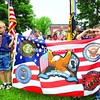 Cub Scout Pack 9 members Kaleb Stewart (left) and James Graziano hold a large flag honoring American militiary branches as part of the Memorial Day parade in Saranac Lake. The parade drew a large crowd to honor the war dead. More photos from Memorial Day events throughout the North Country Page A3. <br><br>(P-R Photo/Jack LaDuke)