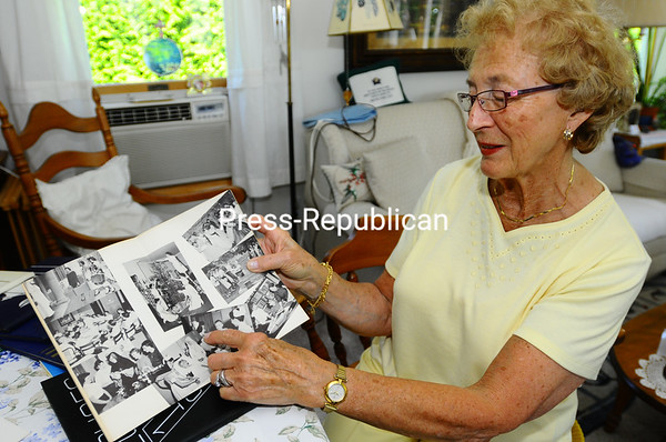 Marceline Kavanagh looks through yearbooks from her days learning to become a nurse at the old Champlain Valley Hospital.<br><br>(Staff Photo/Kelli Catana)