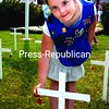 Daisy Scout Nafisa Hadjbekkouche places a poppy on a cross in Windsor Park while the names of departed veterans from Lewis and Elizabethtown are read aloud.<br><br>(Staff Photo/Alvin Reiner)