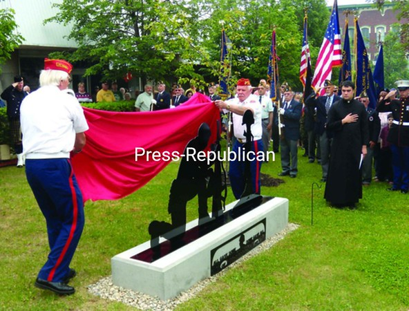 A monument to American troops serving in Iraq and Afghanistan is unveiled during Malone Memorial Day ceremonies. The monument was blessed by the Rev. Bernard Menard of Notre Dame Church (right). Commissioned by Gladys and John Walker of the Have-A-Heart, Adopt-A-Soldier Program, the monument was made by Richard Mongeon.<br><br>(Staff Photo/Denise A. Raymo)