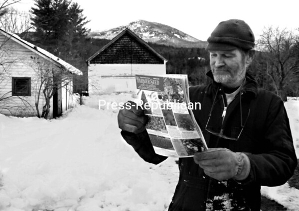 Though snow is evident in the field and mountains by his house in New Russia, Patrick Brady knows it won't be long before he can sow his seeds. He, like many, just received a seed catalog in the mail, indicating spring isn't that far off. Throughout the summer, Brady shares his gardening skills with neighbors.<br><br>(Staff Photo/Alvin Reiner)
