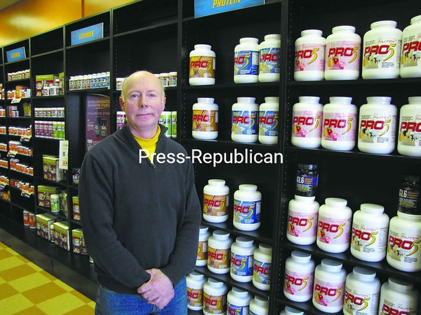 Bob Fiske shows some of the products available at his new store, NutriShop, one of the nation's fastest-growing sports-nutrition, weight-loss and wellness chains, at 47 Smithfield Blvd. in Plattsburgh. Fiske features supplements and top brands for the occasional exerciser, body builder, serious competitor or Ironman athlete. He is open 10 a.m. to 8 p.m. Monday through Saturday and 11 a.m. to 6 p.m. Sunday. Call 324-6996 for more information.<br><br>(P-R Photo/Bruce Rowland)