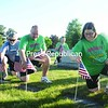 Larry Mills, James Snook, Jennifer LeCuyer, Steve Pierce and Randy Hilliker (from left to right, front to back row)  help place American flags at military veterans' graves Thursday afternoon at Saint Peter's Church Cemetery in Plattsburgh. The volunteers, who were among a group of 10 people from the North Country Biggest Losers fitness organization, assisted Post 20 of the Veterans of Foreign War organization place flags at veterans' grave sites for the Memorial Day weekend.<br><br>(P-R Photo/Andrew Wyatt)