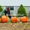 Five-year-old John Paul Corrow uses a pirate hat as the finishing touch on a carved pumpkin while his 3-year-old sister, Megan, inspects each one for a light. The siblings, with the help of their parents, JP and Betty Corrow of Brand Hollow Road in Peru, carved 65 pumpkins which will be lit each night until Halloween, after which they will be used to feed farm animals.<br><br>(P-R Photo/Joanne Kennedy)