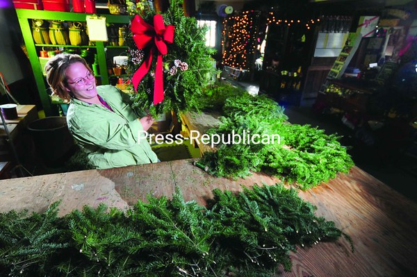 Although Christmas is several weeks away, preparation for the holiday season is well under way at Moody Tree Farm near Saranac Lake. Here, Jessie Genaway checks over a wreath she just made from fresh evergreen boughs. The Tree Farm will turn out about 1,000 of the traditional wreaths before Christmas this year. Handmade wreaths are available at many produce and craft shops around the area.<br><br>(P-R Photo/Jack LaDuke)