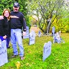 Donna and Bill Downs (above) stand in the graveyard beside their haunted garage. Each tombstone is hand cut, carved and painted. Enter the haunted garage (top right) at 2921 Main St. in Peru — if you dare.<br><br>(Staff Photo/Kelli Catana)