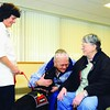 """Shoshi Satloff and her black lab, Bailey, greet Viola Collins and Mary Paul (left to right) during a visit to a waiting room at CVPH Medical Center. Satloff and Bailey have been visiting patients at the hospital for about a year. Paul had a visit from therapy dogs while she was hospitalized. """"If you like animals, it's fantastic,"""" she said.<br><br>(Staff Photo/Kelli Catana)"""