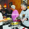 Jean Sklenarik dishes up some gravy onto Maniqa Collins's plate during the Salvation Army's annual Thanksgiving dinner at the Elk's Lodge No. 621 in Plattsburgh.  <br><br>(Staff Photo/Kelli Catana)