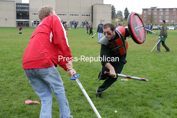"Nick Chakurmanian (right) lunges at fellow Plattsburgh State student Sam McFadden, delivering a crippling blow while defending his realm Sunday afternoon during the first-ever L.A.R.P. (live action role play) event on the field behind Memorial Hall. The objective was to steal the opposing team's treasure from their castle and hold it for five minutes in order to secure a victory. During battle, a hit to the torso resulted in a ""kill"" and a blow to a limb made it unusable, while an additional strike to any part killed that player. Fallen warriors could also be resurrected by a mana (magic) user on their team.<br><br>(P-R Photo/Gabe Dickens)"