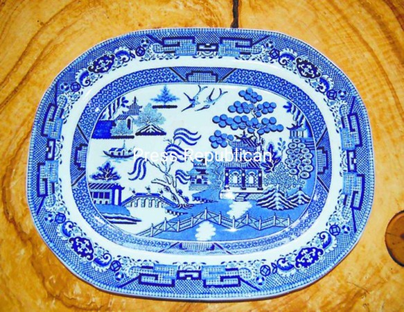 All the details of the forbidden romance between the Chinese maiden Koong-shee and her Mandarin father's lowly accountant Chang, can be found on this English 1860s Blue Willow platter: the willow tree, about to drop its blossoms; the house behind the palace; the separation fence. Also, find the bridge and fleeing lovers, pursued by the father, the boat the couple took to their secluded island home, and the birds they were transformed into at death.   <br><br>(P-R Photo/Julie Robinson Robards)