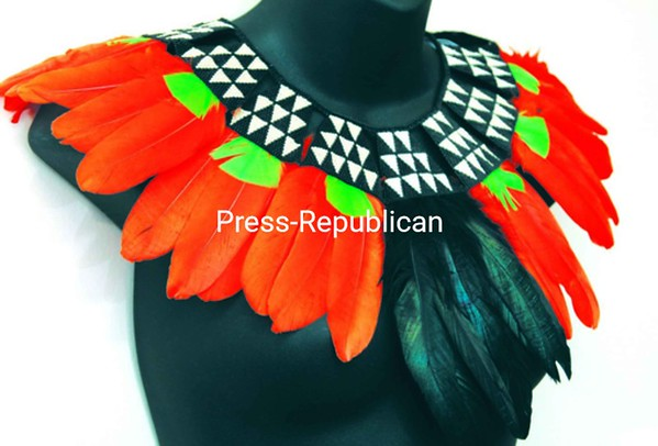 Diane M. Fitzgerald fashioned this elegant Amazon Collar with Peyote stitch fastening black and white beads in a repeating triangular pattern attached to orange, green and black feathers. <br><br>(P-R Photo/Gabe Dickens)