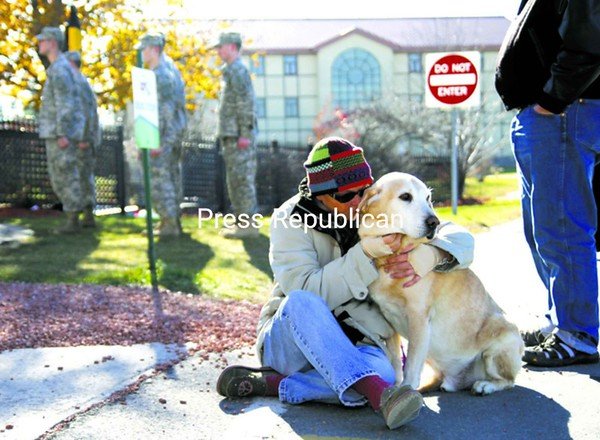 """Terri Cummings of Plattsburgh, an associate professor at Clinton Community College, embraces her golden retriever Happy as she tears up during a ceremony on campus Thursday afternoon, while her brother, Jack Zedaker of Tonganoxie, Kansas, looks on. Her husband, Major Robert Cummings, and father, Major Dahl Zedaker, were stationed at the former Plattsburgh Air Force Base and served in the Vietnam War, while Jack, a major in the Army, is a veteran of Desert Storm. Terri said she is grateful they all returned home safely, although she has had enough of sending loved ones to war. """"No more,"""" she said.<br><br>(P-R Photo/Gabe Dickens)"""