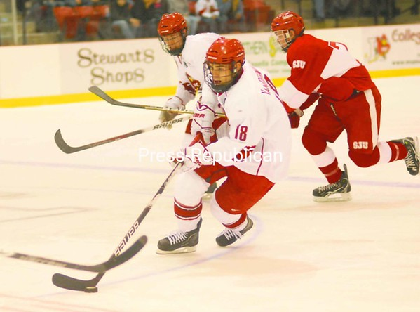 Plattsburgh State's Kyle VanDermale (19) skates away from St. John's Justin Brausen (7) during Friday's opening-round contest in the Annual PrimeLink Great Northern Shootout at the Stafford Ice Arena. The Cardinals outscored the Johnnies, 5-1, over the final two periods for a 7-4 victory.<br><br>(P-R Photo/Andrew Wyatt)