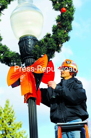 Jordon Hicks, a lineman for the Plattsburgh Municipal Lighting Department, wraps up the downtown holiday decorating by straightening a bow on one of the wreaths lining Margaret Street. <br><br>(Staff Photo/Kelli Catana)