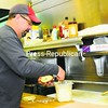 Tony Galloro, chef/owner at Baxter's Bagels in Plattsburgh, puts a topping on one of the bagels offered at the Brinkerhoff Street restaurant.<br><br>(P-R Photo/Chris Fasolino)