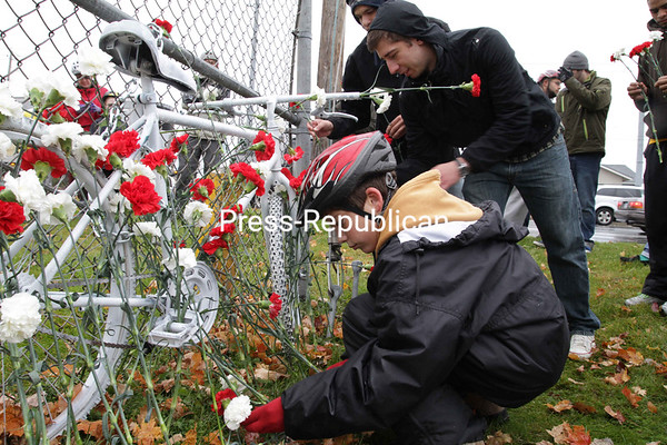 "Liam Vogl, 13, of Plattsburgh and George Schock, a Plattsburgh State student, lay flowers on a ""ghost bike"" dedicated to Yee Hao ""Bryan"" Chiel. The roadside memorial was placed near the on-ramp for Exit 37 where Chiel was killed last month by a tractor-trailer while riding his bicycle. The ceremony was part of Petal to Protect — an event sponsored by the college's Biketopia club to promote bike safety and advocate for safer streets for cyclists. Ghost bikes, a tradition that started in 2003 in Missouri, are usually junk bikes painted white and chained to a location near an accident to serve as a somber reminder of bike tragedies and to support cyclists' rights.<br><br>(P-R Photo/Gabe Dickens)"