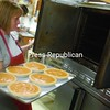 Cheryl Wood balances a tray of pumpkin pies destined for a 350-degree oven inside Banker Orchards kitchen.<br><br>(P-R Photo/Andrew Wyatt)