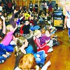 "Annmarie Curle, Oak Street Elementary School physical-education teacher and Reading Incentive Program director, hands out newspapers at an assembly this week to kick off the reading program. This year's theme is ""Extra, extra, read all about it,"" and teachers at the Plattsburgh school are encouraging students to read 40 books from Monday through the end of the school year.<br><br>(Staff Photo/Kelli Catana)"