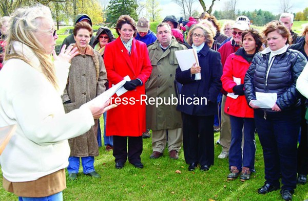Jean Breed (left) read a poem about the Champlain Bridge Saturday at a rally near the demolished span. Listening (from left) are Assemblywoman Teresa Sayward, Vermont House Representative Diane Lanpher, Crisis Program Advocacy Director Rich Couch, Crown Point Supervisor Bethany Kosmider, and Lake Champlain Bridge Coalition members Lorraine Franklin and Lisa Cloutier.<br><br>(Staff Photo/Lohr McKinstry)