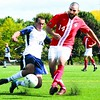 Plattsburgh State's John LoGuirato (14) kicks the ball away from Geneseo's Ryan Yurchak in SUNYAC men's soccer action at the Field House complex Saturday. Plattsburgh went on to 3-0 victory.  <br><br>(P-R Photo/Andrew Wyatt)