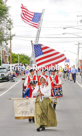 Girl Scout Troop 4040 (above) marches in the Port Henry Labor Day Parade Sunday. The giant American flag behind the Crown Point Fife and Drum Corps (right)  is part of the Hudson Falls-based MacBoston Truck Boosters' tribute to fallen firefighters. For more Labor Day coverage and event listings, see page A3.<br><br>(Staff Photo/Lohr McKinstry)