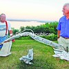 Port Henry residents Dale Henry (left) and Jeff Kelly show the scrap-metal sculpture they created from pieces of the old Champlain Bridge. The new bridge is under construction on the lake behind them. The sculpture sits on Henry's lawn on Spring Street in Port Henry.<br><br>(Staff Photo/Lohr McKinstry)