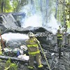 Schroon Lake firefighters try to douse a fire that destroyed a seasonal home on Kanasta Cove off Route 9 Wednesday morning. William and Leslie Otto of Westchester County own the camp. They were not there at the time but had apparently visited last week. Crews from Schroon Lake, Ticonderoga, Pottersville and North Hudson were unable to save the structure. The cause of the fire had not been determined Wednesday.<br><br>(Staff Photo/Alvin Reiner)