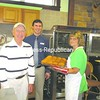 Maureen Cane (right) takes some fresh-baked rolls out of the oven at her new business, Everything Sweet Bakery and Cafe, at Maggy's Marketplace in Dannemora. Cane took over the bakery from marketplace owners Skip Maggy (left) and Mark Maggy, who are doing their best to help her be successful.<br><br>(P-R Photo/Bruce Rowland)