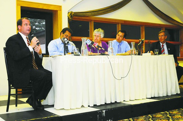Republican congressional candidate Matt Doheny (left) answers a question at Wednesday night's debate with opponent Douglas Hoffman (far right). The candidates answered questions from media panelists (from left) Joe LoTemplio of the Press-Republican, Pat Bradley from WAMC and Jeremiah Papineau of Denton Publications.<br><br>(Staff Photo/Kelli Catana)