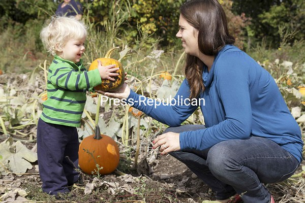 Kelly Higgs of Chateaugay, Quebec, finds the perfect pumpkin for her 14-month-old son, Ryder, at Country Dreams Farm in Plattsburgh Sunday afternoon. They were part of a larger group that made the trip down from Canada to visit the farm.<br><br>(P-R Photo/Gabe Dickens)