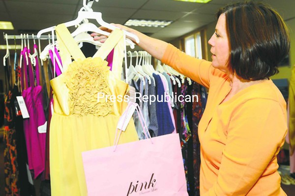 Leigh Mundy, president of the board at the North Country Cultural Center for the Arts, arranges clothing for the Frugal Fashionistas event to benefit the Strand Performing Arts Center. Clothing for the sale, held Thursday evening, was donated by local individuals, as well as some businesses, including Pink from Saranac Lake, Lola's Closet, Maui North and Lotusgrace at Lakeshore Candy. Facial products were donated by Dr. Oliva's office, food from Michelle's Fine Dining and Olive Ridleys and wine from Vesco Ridge. A steady stream of shoppers came through during the night.  <br><br>(Staff Photo/Kelli Catana)