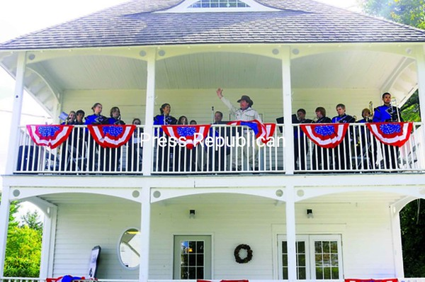Thomas Mandeville (center), professor of history at Clinton Community College, portrays President Theodore Roosevelt as he delivers a Constitution Day speech from the balcony of the Pines Cottage at CCC. He was accompanied by the Peru High School Marching Band. The open house at Pines Cottage gave visitors the opportunity to meet Community and Workforce Development staff,  tour the facility and learn more about the programs offered there. <br><br>(Staff Photo/Kelli Catana)