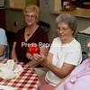 Dot Perry holds a triplet tomato given to her by Edna McCabe (second from left). McCabe's sisters, Lillian Cayea (far left) and Dot Giroux (far right) were among those attending the Open House at the Senior Center in Plattsburgh.<br><br>(Staff Photo/Robin Caudell)