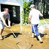 Cory Hanf shovels mud while his wife, Sierra, heads back to the garage to push out another load from their property in AuSable Forks.<br><br>(Staff Photo/Alvin Reiner)