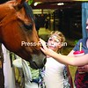 Amanda Montgomery (middle) and her daughters Riley White (left), 8, and Breanne Allen, 11, of Massena spend some time with a curious quarter horse named Girl Scout Cookie at the Franklin County Fair. Cookie, who is in her sixth year at the fair, does a bit of everything, including games classes, English and Western horse shows, as well as jumping.<br><br>(P-R Photo/Gabe Dickens)