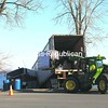 Workers attempt to empty a tractor trailer as it lies jackknifed on the rocks several feet from the waters of Lake Champlain Monday afternoon. Scott Bachard, a patrolman with the Rouses Point Police Department, said the driver likely fell asleep at the wheel around 5 a.m. Monday in Rouses Point and veered off Lake Street near Stewart's Shop, jumping the curb. The driver, who wasn't hurt, was hauling processed dry milk to Swanton, Vt. Crews had to drain the gas tank, which was lodged between large rocks and the cabin, in case it ruptured while the truck was pulled out. <br><br>(P-R Photo/Gabe Dickens)