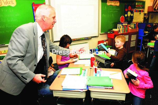 Plattsburgh Noon Kiwanis Club President Rob Shumway hands out dictionaries to Oak Street Elementary School third-graders (from left) Harley Staley, Brandt Clarke and Natalie Kay Thursday. The annual project hands out dictionaries to third graders in Seton Academy; and Momot, Oak Street, Morrisonville and Saranac elementary schools. <br><br>(P-R Photo/Rob Fountain)