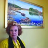 """Pamela May stands next to """"Spring on Gourd Shell Pond,"""" one of the oil paintings she recently donated to Franklin County. It hangs in the County Legislature conference room along with her other donated piece, """"Owls Head Sunrise."""" <br><br>(Staff Photo/Denise A. Raymo)"""