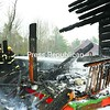 Firefighters spray down the remains of Peter Boushie's log home on Mitchell Lane in Tupper Lake on Thursday. The structure was a complete loss.<br><br>(P-R Photo/Jack LaDuke)