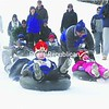 Wearing his royal hat as part of the 114th Winter Carnival court, third-grader Jacob Adams of Saranac Lake gets off to a fast push-start at the annual inntertube race held on Mount Pisgah Friday. Scores of youngsters took part in the popular event. <br><br>(P-R Photo/Jack LaDuke)