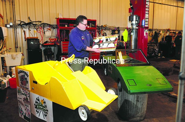 Bob Bevilacqua of Saranac Lake looks over a Soap Box Racer Kit that he will use to build a gravity-powered racer as part of the first-annual Daffodil Festival, set for April 30. Two of the sleek racers, already built, stand in front of him. The race will be held on a quarter-mile stretch of the Lapan Highway in downtown Saranac Lake. More information can be found at www.daffest.com. <br><br>(P-R Photo/Jack LaDuke)